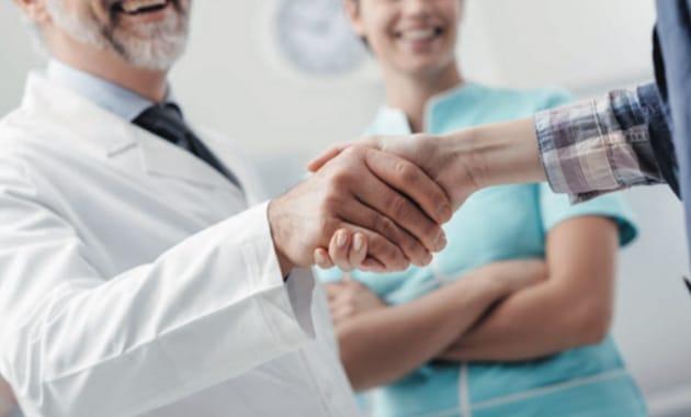 un docteur serre les mains d'une assistante