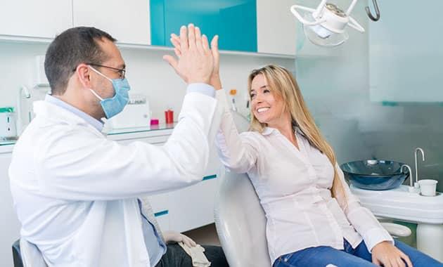 dentiste tapant dans la main d'un patient