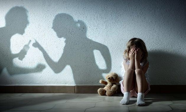 petite fille pleurant devant ombre de ses parents se disputant
