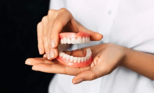 Le dentiste tient des prothèses dentaires dans ses mains.